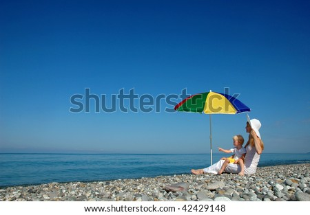 Woman with child under umbrella on the beach