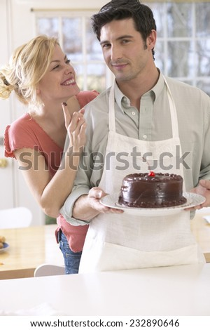 Woman with Chocolate Icing on her Finger next to Boyfriend Holding Cake - stock photo
