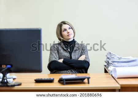 Woman with clasped hands dreaming at working place - stock photo