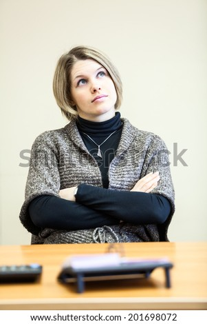 Woman with clasped hands sitting on workplace - stock photo