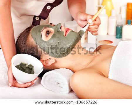 Woman with clay facial mask in beauty spa. - stock photo
