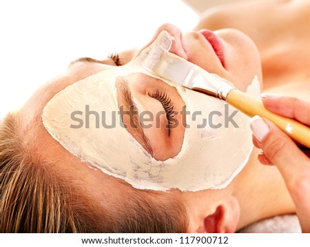 Woman with clay facial mask in beauty spa. Isolated. - stock photo
