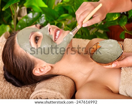 Woman with clay facial mask in beauty spa.Towel under the neck - stock photo