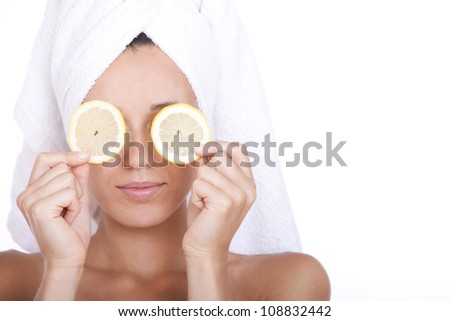 Woman with clean face is holding two slices of lemon over white background - stock photo