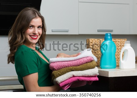 Woman with clean towels, basket and various washing detergents - stock photo