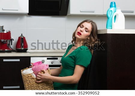 Woman with clean towels, basket and various washing detergents