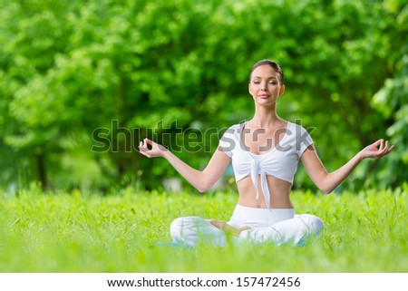Woman with closed eyes sits in lotus position zen gesturing. Concept of healthy lifestyle and relaxation