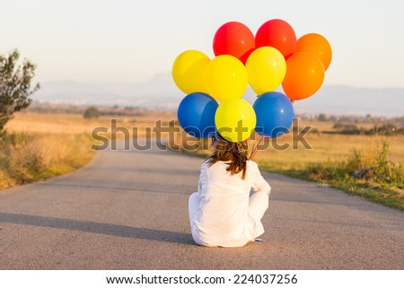 Woman with colorful ballons in her hand on the road - stock photo