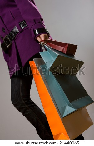 Woman with colorful shopping bags over grey - stock photo