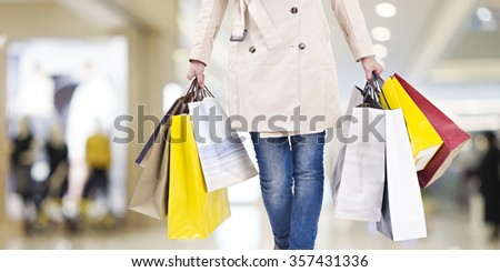 woman with colorful shopping bags walking in modern mall. - stock photo