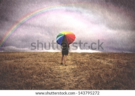 Woman with colorful umbrella in the rain for the field