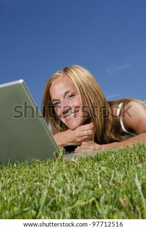 Woman with computer in the grass towards blue sky