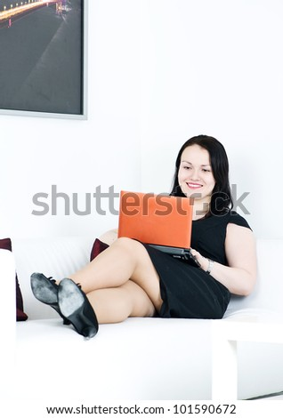 Woman with computer on the sofa - stock photo