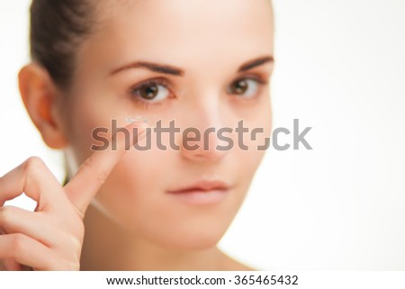 Woman with contact lens on finger, healthcare concept