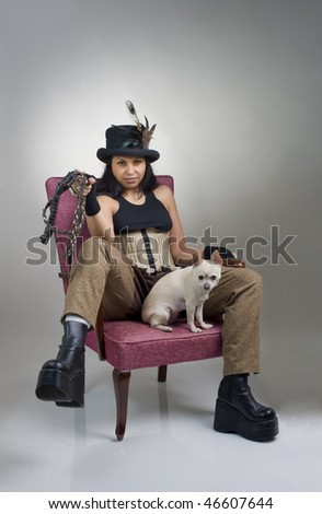 woman with corset breeches hat dog and whip on armchair - stock photo