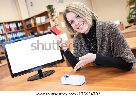 Woman with credit card and gift thinking about internet shopping  - stock photo