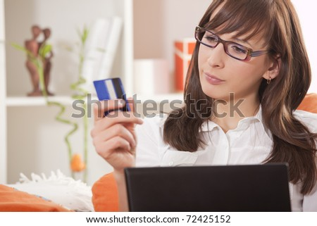 woman with credit card and laptop thinking about internet shopping - stock photo
