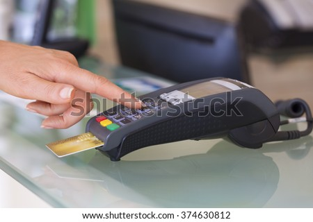 Woman with credit card swipe through terminal, security code - stock photo