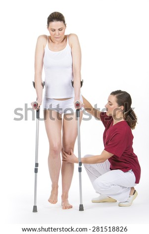 woman with crutch at the physiotherapist doing legs rehabilitation - stock photo