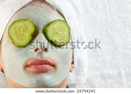 Woman with cucumbers and face mask - stock photo