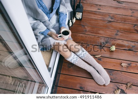 Woman with cup of coffee sitting relaxing home in the window, she's covered in a blanket. Fall leaves on wooden patio deck. Autumn concept.