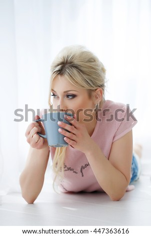 woman with cup of tea laying on floor at home.