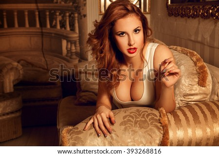 Woman with curly hair and big natural boobs in white dress looking at the camera indoors. Seductive woman. Sexual woman. the concept of seduction, pleasure and desire - stock photo
