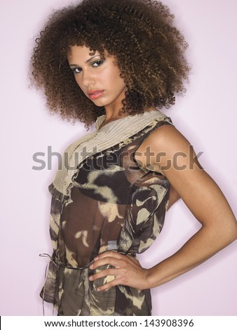 Woman with curly hair and hands on hips standing against pink background - stock photo