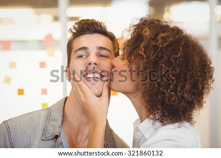 Woman with curly hair kissing shocked businessman in creative office - stock photo