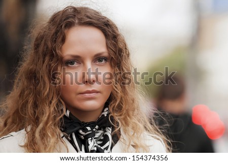 Woman with curly hairs on the city street - stock photo