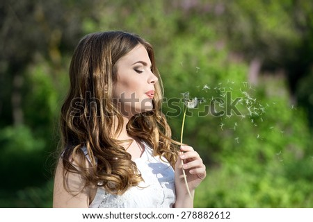woman with dandelion in sunny day