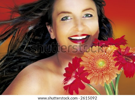 woman with dark hair holding flowers. wind is blowing. - stock photo