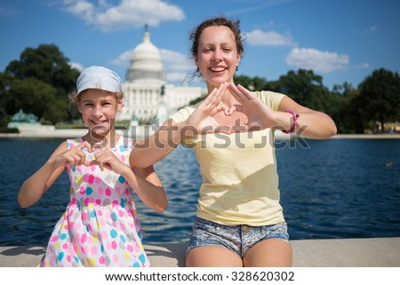 Woman with daughter depict hearts near pond and Capitol at summer. - stock photo