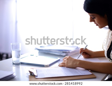 Woman with documents sitting on the desk - stock photo