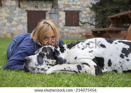 Woman with dog lying on the green grass in the park. great dane dog breed - stock photo