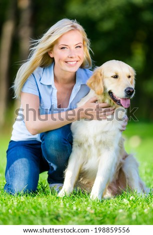 Woman with dog sitting on the green grass in the summer park - stock photo