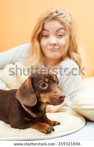 Woman with dog waking up in the morning after sleeping. Young girl laying in bed.