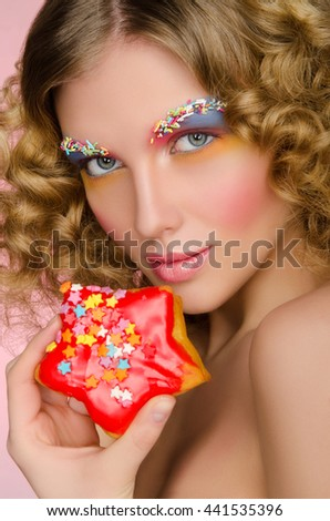 woman with donut in face on pink background