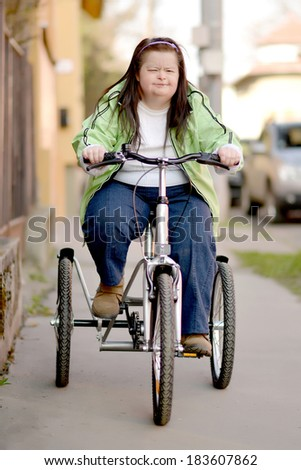 woman with down syndrome riding bike tricycle - stock photo