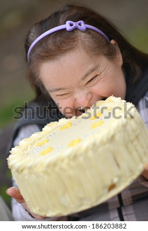 woman with down syndrome with birthday cake - stock photo