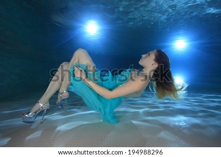 Woman with dress posing underwater in the pool  - stock photo