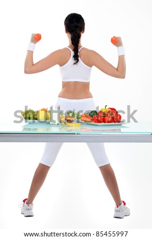 Woman with dumbbells and plates of salad and fruit - stock photo