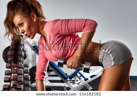 Woman with dumbbells in sport center - stock photo