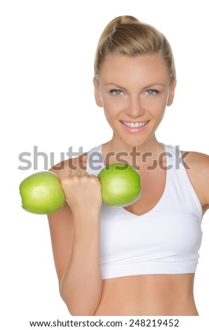 Woman with dumbbells of green apples isolated on white - stock photo