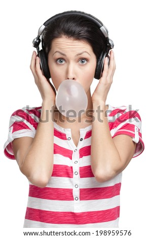 Woman with earphones blows out a bubble gum, isolated on white - stock photo