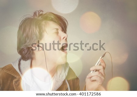 Woman with earphones listening to music and singing;  - stock photo
