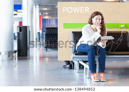 Woman with electronic devices near place to charge your phone - stock photo