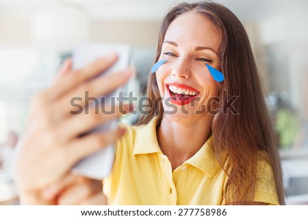 "woman with ""emoji"" style tears of her laughing face. woman reading jokes in internet from mobile phone - stock photo"