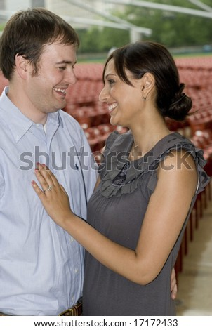 Woman with engagement ring embracing man - stock photo