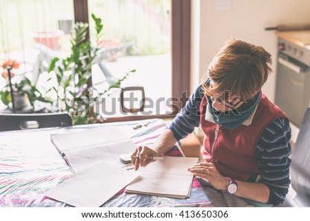 Woman with eyeglasses sitting at table, reading and handwriting paperwork and documents. Selective focus, home interiors. Concept of working at home. - stock photo